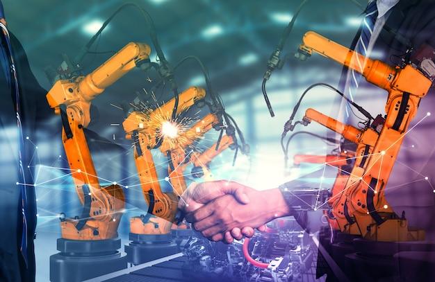 Mechanisierter industrieroboterarm und geschäftshändedruck doppelbelichtung