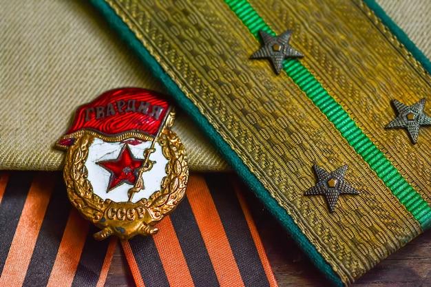 Medaille und schulterklappen eines udssr-soldaten des zweiten weltkriegs, hintergrund des siegestages