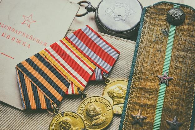 Medaillen, schulterklappen und armeeausweis eines udssr-soldaten des zweiten weltkriegs, hintergrund des siegestages.