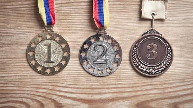 Medaillenpreise für gewinner auf holzhintergrund