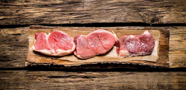 Medaillons von rohem fleisch auf der rinde eines baumes. auf hölzernem hintergrund. draufsicht