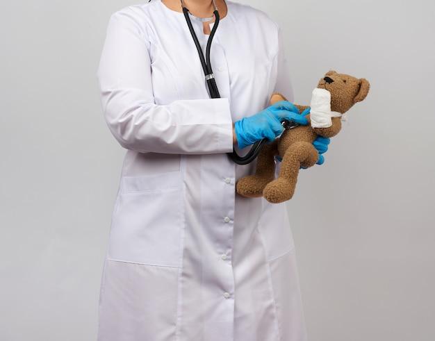 Medic hält einen braunen teddybär mit einer pfote in einem weißen verband und hört zu, wie er mit einem stethoskop spielt