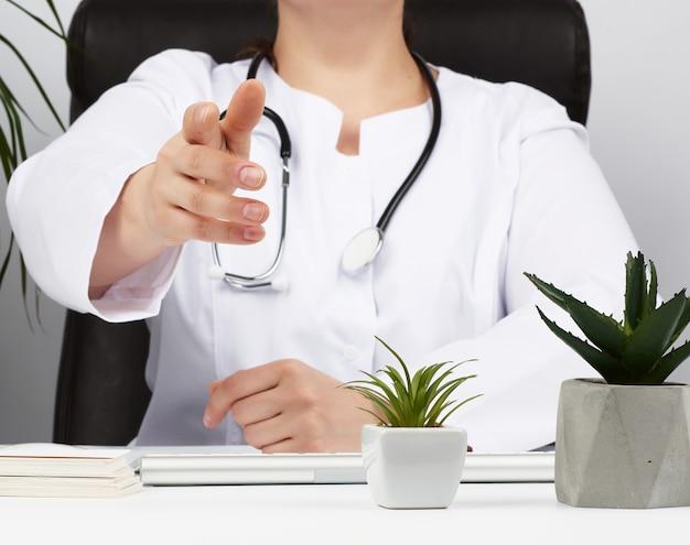 Medic in einem weißen kittel sitzt an einem tisch und zieht seine rechte hand zum händedruck nach vorne