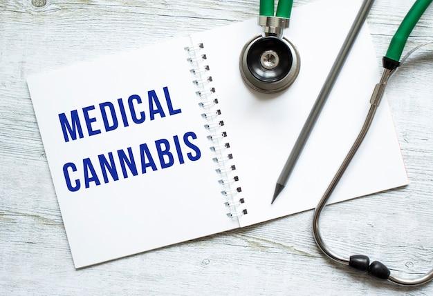 Medical cannabis steht in einem notizbuch auf einem hellen holztisch