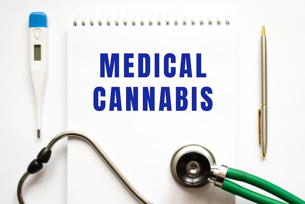 Medical cannabis text geschrieben in einem notizbuch, das auf einem schreibtisch und einem stethoskop liegt. medizinisches konzept.