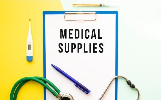 Medical supplies text auf einem briefkopf in einem medizinischen ordner auf einem schönen hintergrund. stethoskop, thermometer und stift.
