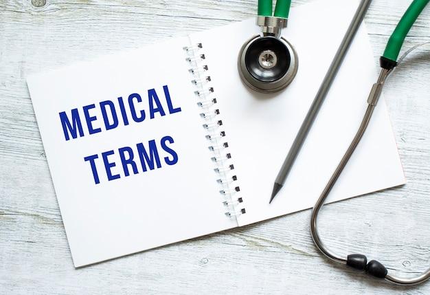 Medical terms steht in einem notizbuch auf einem hellen holztisch neben bleistift und stethoskop. medizinisches konzept