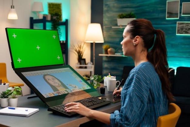 Medienprojektkünstler, der mit grünem bildschirm auf dem display arbeitet