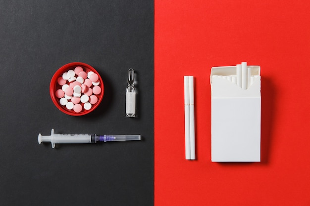 Medikamente bunte runde tabletten pillen, leere spritzennadel, ampulle, packung zigaretten