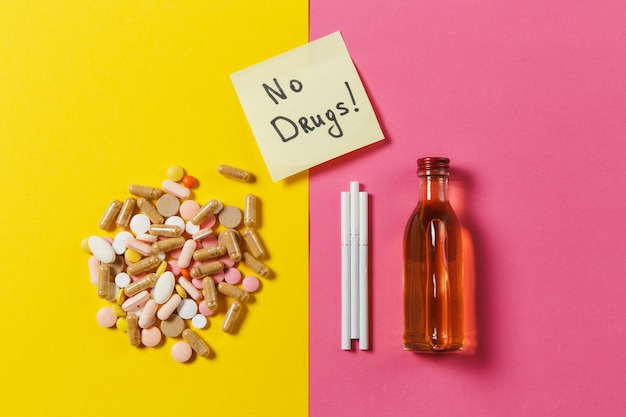 Medikamente bunte tabletten pillen angeordnet abstrakt, flaschenalkohol, zigaretten auf gelbem rosa rosenhintergrund. papieraufkleberblatt textwort keine drogen. behandlung, wahl gesunder lebensstil. platz kopieren.