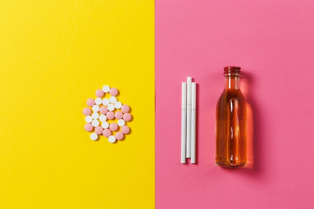 Medikamente bunte tabletten pillen arrangiert abstrakt, flasche alkohol, cognac, whisky, drei weiße zigaretten auf gelbem rosafarbenem hintergrund