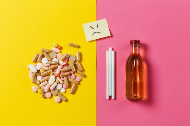 Medikamente bunte tabletten pillen arrangiert abstrakt, flaschenalkohol, zigaretten auf gelbem rosafarbenem hintergrund