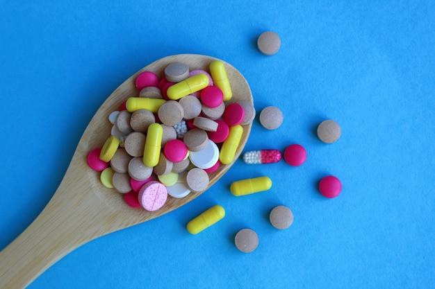 Medikamente in form von tabletten und kapseln liegen auf einem haufen auf einem holzlöffel an einer blauen wand. das thema ist der medizinlöffel. schaden und nutzen.