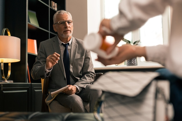 Medikamente nehmen. senior psychologe sitzt auf einem stuhl, während er seine patientin genau beobachtet, die in seiner gegenwart antidepressiva einnimmt