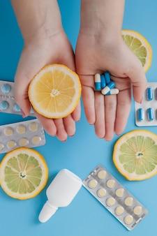 Medikamente, pillen, thermometer, traditionelle medizin zur behandlung von erkältungen, grippe, hitze an einer blauen wand. aufrechterhaltung der immunität. saisonale krankheiten. draufsicht. medizin flach lag