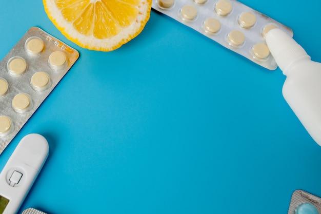 Medikamente, pillen, thermometer, traditionelle medizin zur behandlung von erkältungen, grippe, hitze auf blauem grund. aufrechterhaltung der immunität. saisonale krankheiten. ansicht von oben. medizin flach liegen