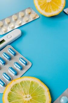 Medikamente, pillen, thermometer, traditionelle medizin zur behandlung von erkältungen, grippe, hitze auf einem blauen. aufrechterhaltung der immunität. saisonale krankheiten. ansicht von oben. medizin flach liegen