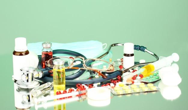 Medikamente und ein stethoskop auf einem grün