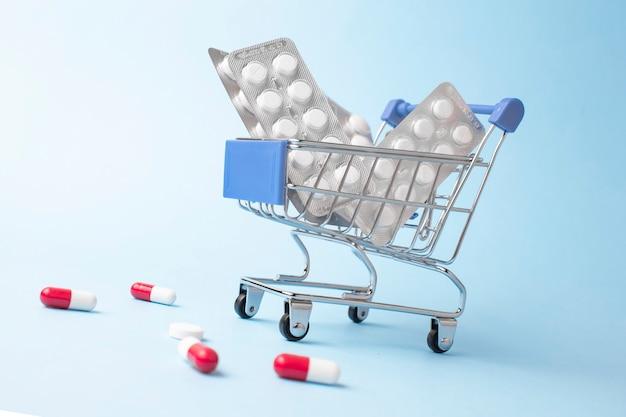 Medikamente, vitamine und antioxidative nahrungsergänzungsmittel im trolley oder warenkorb online auf blauer oberfläche