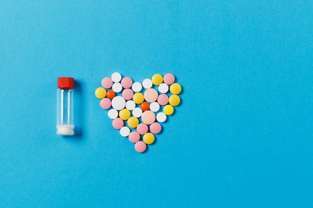 Medikamente weiße, bunte runde tabletten in form von herzen auf blauem hintergrund isoliert