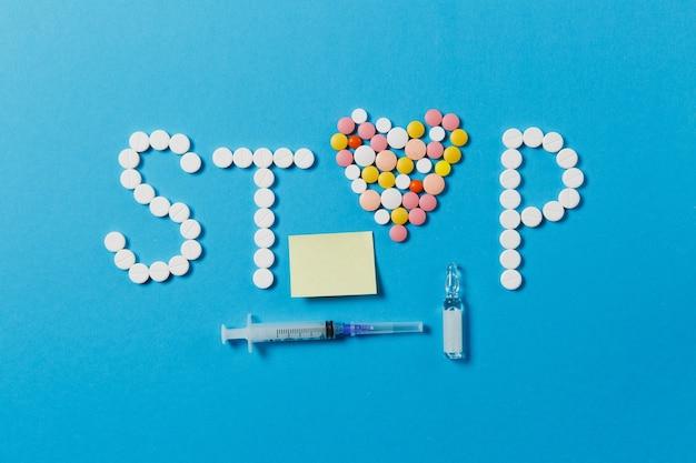 Medikamente weiße, bunte runde tabletten in wort stop auf blauem hintergrund isoliert