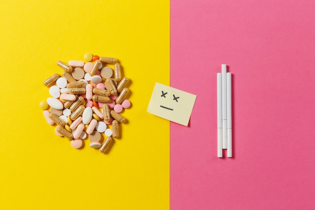 Medikamente weiße bunte runde tabletten pillen angeordnet abstrakt drei zigaretten auf gelbem hintergrund