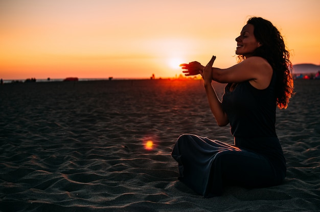 Meditation der jungen frau auf sonnenuntergangstrand