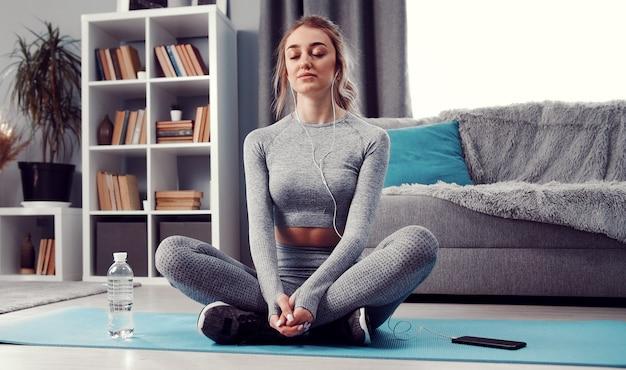 Meditative dame mit geschlossenen augen, die mit gefalteten beinen auf übungsmatte auf dem boden sitzt und musik hört