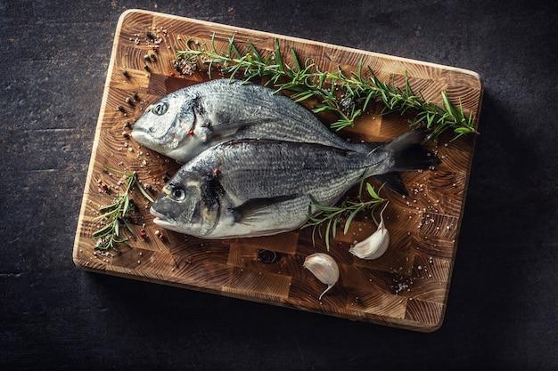 Mediterrane fischbrasse mit gewürzen salz kräuter knoblauch und zitrone. gesunde meeresfrüchte. konzept der gesunden meeresfrüchte.