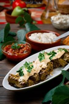 Mediterrane küche - dolma in teller mit frischem koriander und sauce auf dunklem holztisch, seitenansicht in nahaufnahme. dolma, traditionelles gericht aus fleisch und weinblättern - kaukasische, türkische und griechische küche
