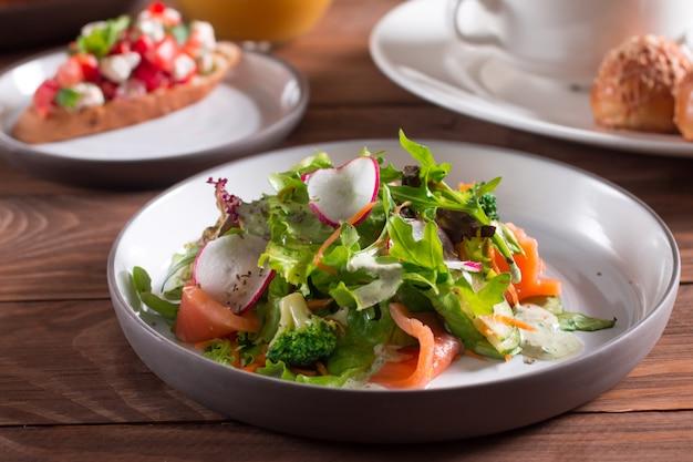 Mediterrane küche. salat. lachsscheiben mit frischem gemüsesalat auf einem teller.