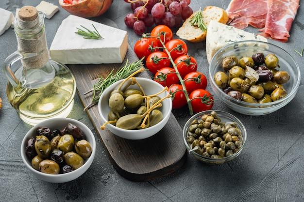 Mediterrane oliven und kapern mit kräutern auf grauem tisch
