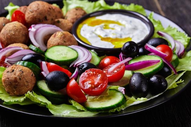 Mediterrane platte mit falafel, tomaten, gurken, roten zwiebeln, schwarzen oliven, auf den frischen salatblättern serviert mit tzatziki-sauce serviert auf einem schwarzen teller auf dunkler holzoberfläche, nahaufnahme close