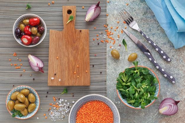 Mediterrane snacks eingestellt. grüne und schwarze oliven, laib frisches mehrkornbrot, feldsalat und rote zwiebeln über altem holzhintergrund. draufsicht mit platz für text. flach liegen.