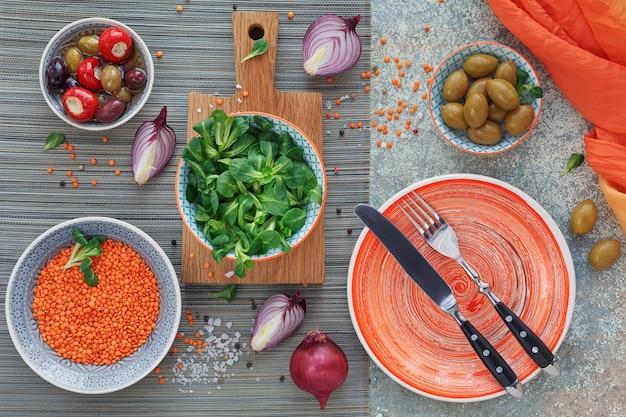 Mediterrane snacks eingestellt. grüne und schwarze oliven, laib frisches mehrkornbrot, feldsalat und rote zwiebeln über altem holzhintergrund. draufsicht mit platz für text