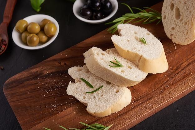 Mediterrane snacks. oliven, öl, kräuter und geschnittene ciabatta auf einem holzbrett auf schwarzem schiefersteinbrett über dunkler oberfläche, draufsicht. flach liegen.