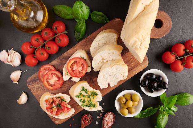 Mediterrane snacks. oliven, öl, kräuter und geschnittenes ciabatta auf einem holzbrett auf schwarzem schiefersteinbrett über dunkler oberfläche, saftige tomaten auf frischem brot, pesto als belag. draufsicht. flach liegen