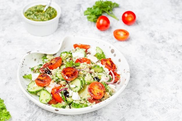 Mediterraner couscous-salat mit gebratenen kirschtomaten, gurken-pesto-sauce