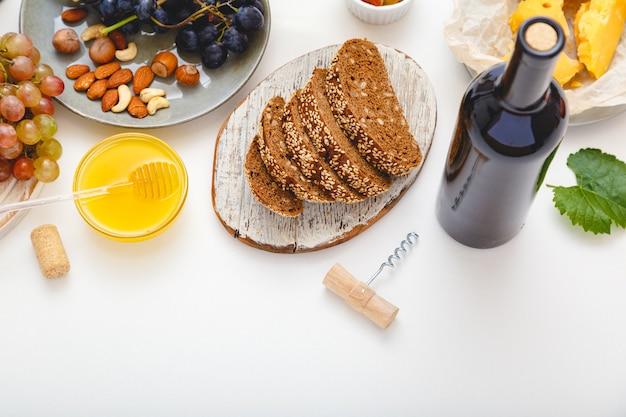 Mediterranes essen am esstisch wein vorspeise honig käse nüsse snacks brot trauben obst