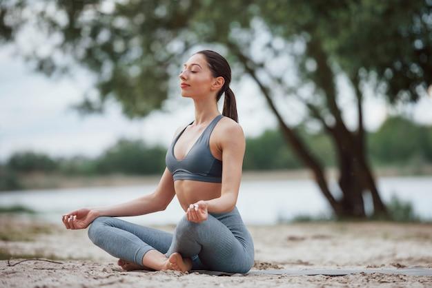 Meditieren mit geräuschen der natur. brünette mit schöner körperform in sportlicher kleidung haben fitness-tag am strand