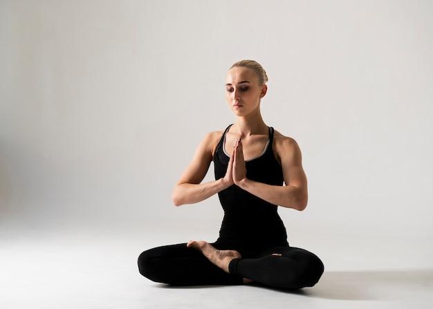 Meditierende haltung der vollen schussfrau