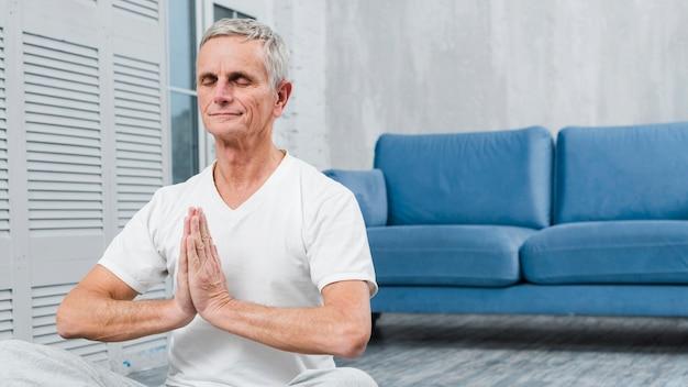 Meditierender älterer mann mit den betenden händen