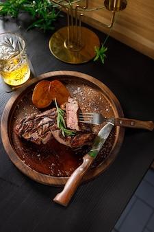 Medium rare steak on bone kalbsrippe mit kartoffel auf einer holzplatte
