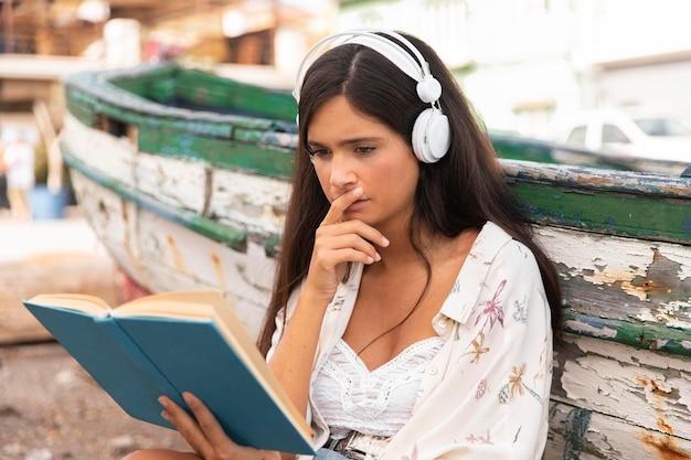 Medium schuss mädchen mit kopfhörern lesen