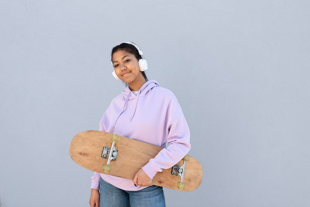 Medium shot girl mit kopfhörern und skate