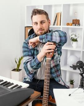 Medium shot musiker posiert mit gitarre
