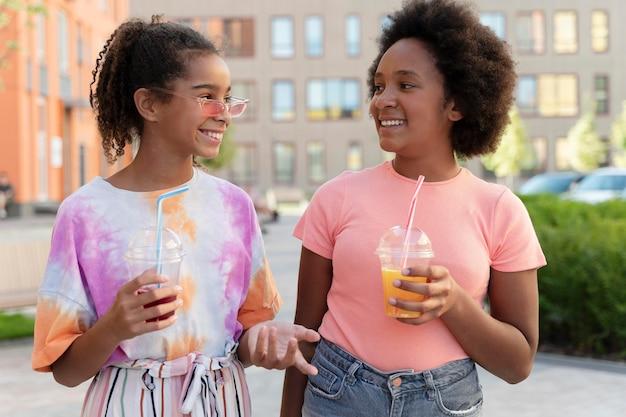Medium shot smiley girls mit drinks