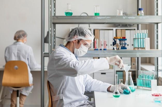 Medium shot wissenschaftler bereitet lösung vor