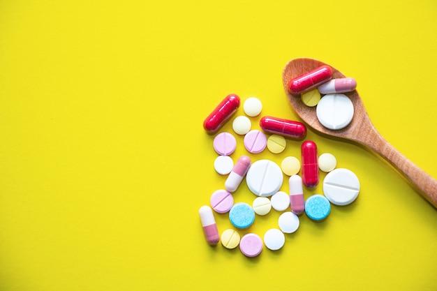Medizin auf hölzernem löffel und herz formte pille Premium Fotos