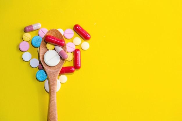 Medizin auf hölzernem löffel und herz formte pille
